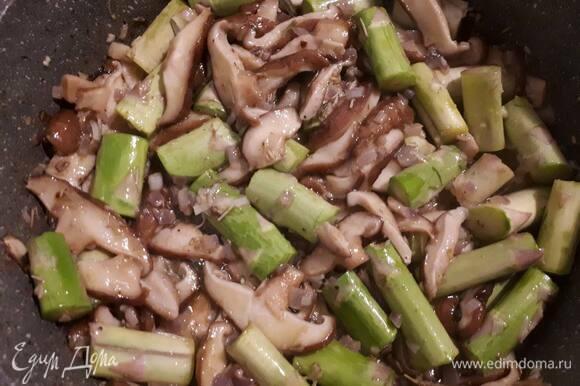 Отрежьте у спаржи жесткую нижнюю часть. Оставшиеся стебли нарежьте на бруски, добавьте к грибам и обжарьте 5 минут. Затем убавьте огонь, накройте крышкой и оставьте на 10 минут.