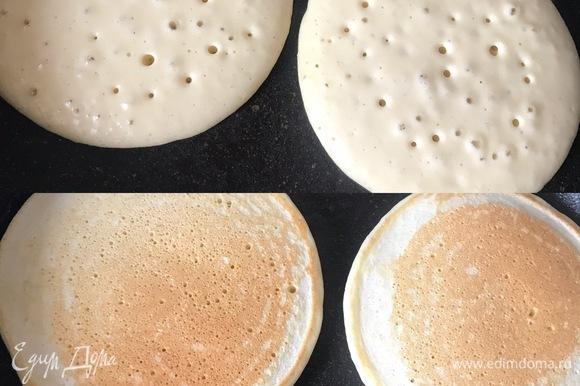 Блины можно готовить сразу, а можно дать тесту постоять 15–30 минут. Сковороду хорошо разогреть, слегка смазать маслом и начать жарить блины. В сковороду выложить 3–4 ст. л. теста, убавить огонь и жарить блины. Когда на поверхности появятся пузырьки и поверхность станет матовой, перевернуть блины и жарить еще одну минутку.