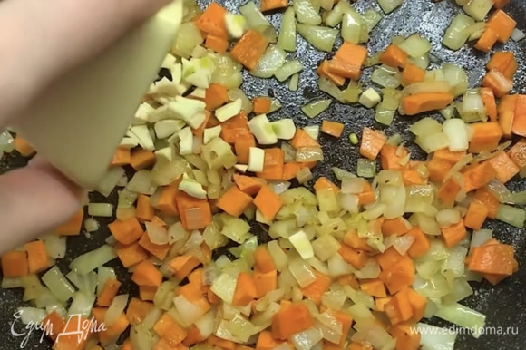 В ту же сковороду с маслом выкладываем нарезанный лук и морковь, обжариваем 5–7 минут. Добавляем чеснок и томаты в собственном соку, накрываем крышкой и тушим около 5 минут.