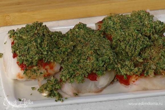 Филе трески смазать томатной пастой, сверху выложить панировку, полить 1 ч. ложкой оливкового масла, посолить и поперчить.