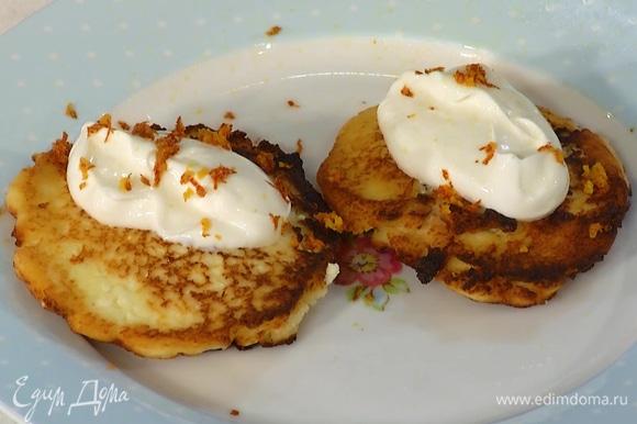 Подавать готовые сырники со сметаной, джемом и цедрой апельсина.