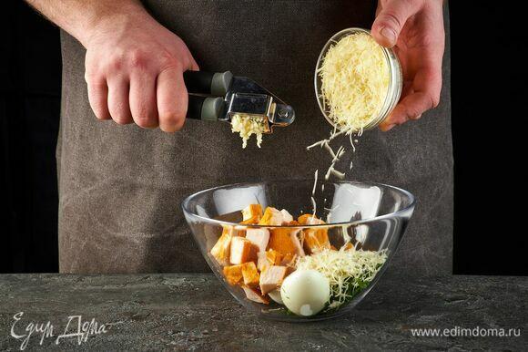 Выложите в салатник. Добавьте тертый сыр и выдавите чеснок.