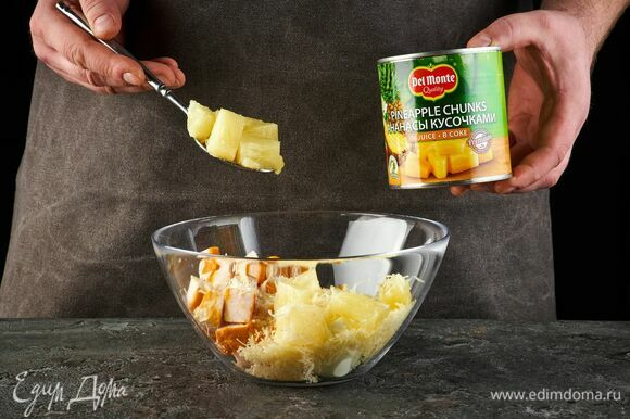 Откройте банку с кусочками ананаса в соке Del Monte, слейте жидкость. Добавьте в салатник.