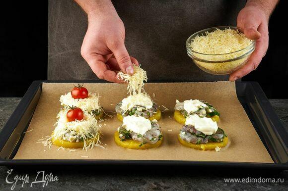 Затем выложите майонез и посыпьте тертым сыром. Украсьте помидорами и запекайте в духовке при 180°C около 10 минут.