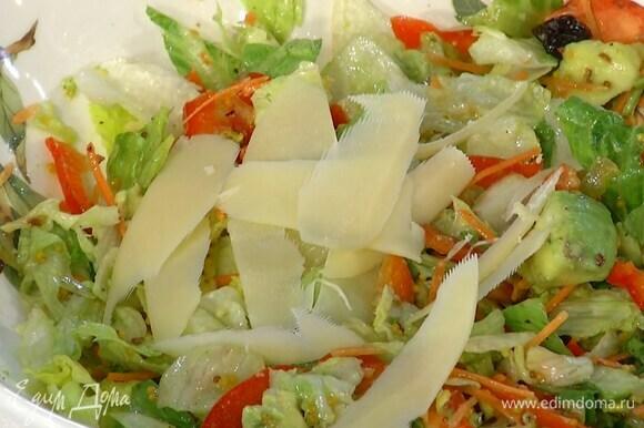 Твердый сыр нарезать тонкими хлопьями и выложить на салат.