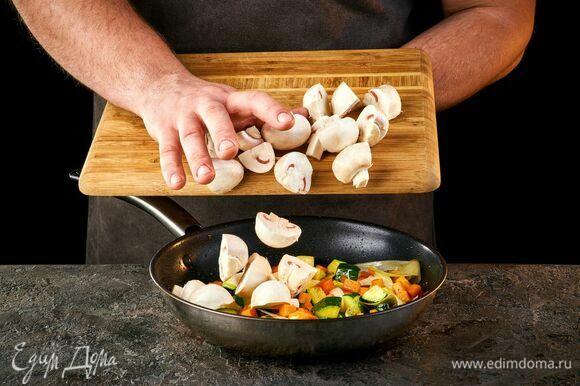 Нарежьте грибы кусочками и добавьте к овощам. Обжаривайте около 15 минут.