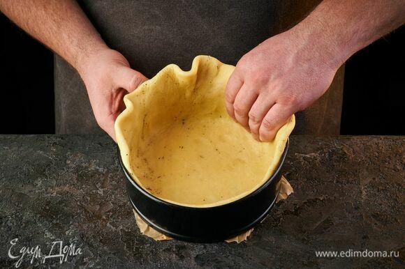 Достаньте тесто из холодильника и распределите его по форме, сформировав бортики. Проколите дно вилкой.