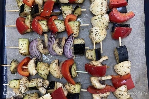 Нанизать овощи на шпажки, разложить на противень, застеленный пергаментом. Сбрызнуть оливковым маслом.