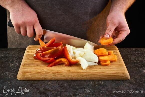 Лук нарежьте полукольцами, болгарский перец — брусочками, морковь — кружками.