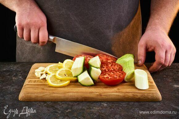 Цукини, помидоры, лук-порей крупно нарежьте. Чеснок мелко порубите, лимон нарежьте кольцами.