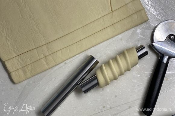 Тесто разрезать на одинаковые полоски диаметром 2 см. Аккуратно накрутить на трубочки.