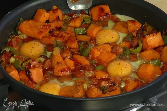 Яйца разбить в сковороду с колбасой и овощами, посолить, поперчить и запекать в разогретой духовке 3–4 минуты.