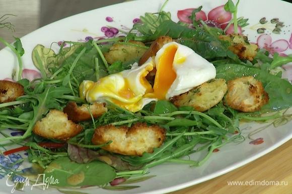 На большую тарелку выложить салатный микс, полить заправкой, сверху выложить крутоны и яйцо пашот.