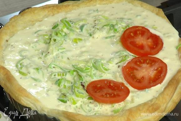 С подпеченного коржа убрать бумагу с бобовыми, равномерно выложить в него половину натертого сыра, затем порей и залить яичной смесью, сверху разложить помидоры, посыпать оставшимся сыром.