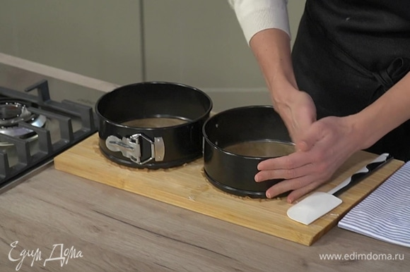 Две круглые разъемные формы застелить бумагой для выпечки, смазать оставшимся сливочным маслом и равномерно выложить тесто.