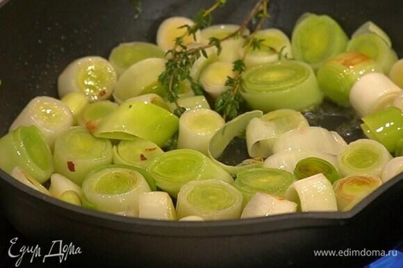 В отдельной сковороде разогреть оливковое масло, выложить лук-порей и веточки тимьяна, посыпать перцем чили и обжарить до золотистого цвета.