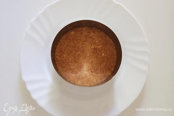 Печенье измельчить до состояния крошки и смешать с растопленным сливочным маслом. На блюдо поставить металлическое кольцо диаметром 12 см, на дно выложить печенье, утрамбовать и поставить в холодильник на 15–20 минут.
