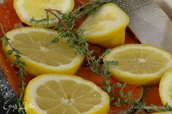 Стейки посолить, посыпать паприкой и уложить в форму для запекания, сверху разложить дольки лимона и веточки тимьяна.