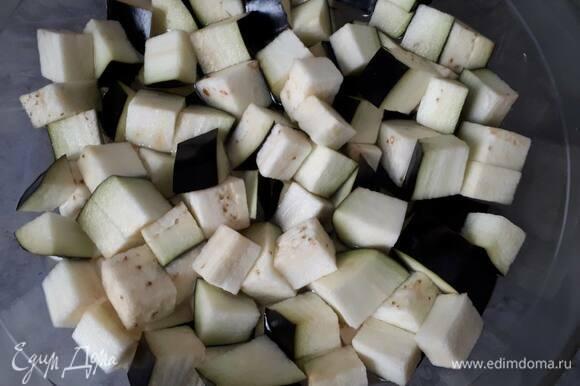 Нарежьте баклажан кубиками и замочите на полчаса в холодной подсоленной воде.