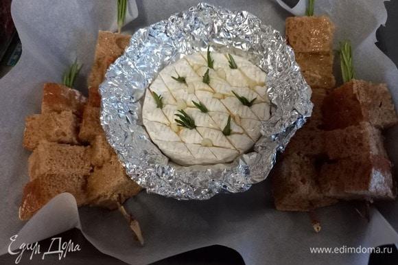 Форму для запекания застилаем пекарской бумагой, выкладываем сыр в фольге и шпажки с хлебом. Хлеб поливаем еще одной чайной ложкой оливкового масла.
