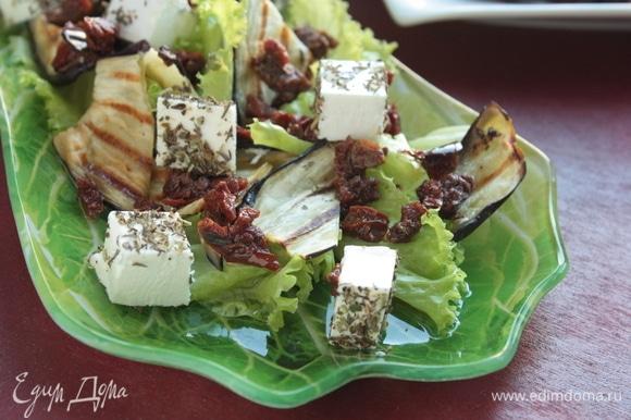 Выложите листья салата, на них распределите баклажаны, вяленые томаты и сыр, сбрызните салат заправкой и наслаждайтесь!