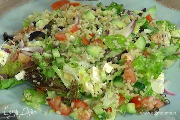 Фету нарезать кубиками, добавить в салат и еще раз перемешать. Готовый салат подавать на большой тарелке.