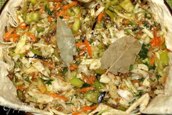 Овощи складываем в миску, добавляем растительное масло и приправы. Все хорошо перемешиваем. Приправы и специи лучше регулировать по своему вкусу. Тонкий лаваш складываем вдвое, кладем в форму для запекания, чтобы получились бортики. Этот процесс можно пропустить, но лаваш впитает весь лишний сок, края подпекутся, и это будет очень вкусно. Перекладываем в форму овощи, разравниваем. Добавляем лавровый лист.