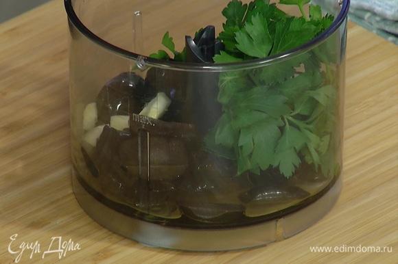 Приготовить пасту: чеснок почистить и выложить в чашу блендера, добавить маслины и петрушку, влить оливковое масло и все измельчить.