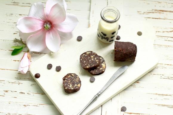 Измельчите подсохшие коржи (лучше вручную, чтобы контролировать величину крошки), смешайте с какао, добавьте крем, орешки и предварительно растопленное сливочное масло (40 г). Тщательно вымесите массу. Выложите на пищевую пленку, сформируйте колбаску и положите ее на 20–30 минут в морозилку, чтобы изделие схватилось. Далее храните в холодильнике.