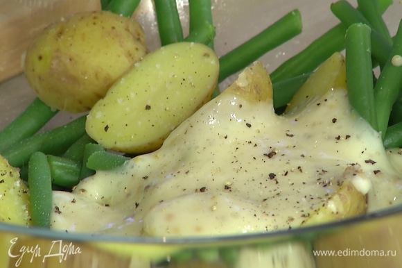 Отваренный картофель нарезать половинками, выложить к фасоли с горохом, заправить майонезом, посолить, поперчить и перемешать.