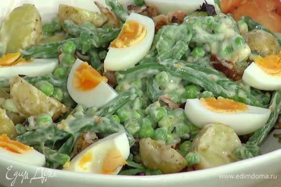 Отваренные яйца нарезать четвертинками и украсить салат.