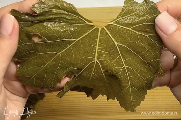 Виноградные листья промываем, отрезаем у каждого листика веточку. Рваные или не очень красивые листики выкладываем на дно кастрюли.