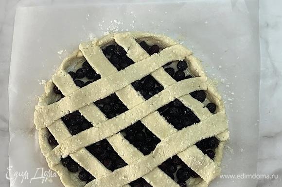 Оставшуюся часть теста раскатываем, нарезаем на полоски и украшаем пирог «сеточкой». Выкладываем на противень и отправляем в заранее разогретую до 180°C духовку на 20–25 минут.