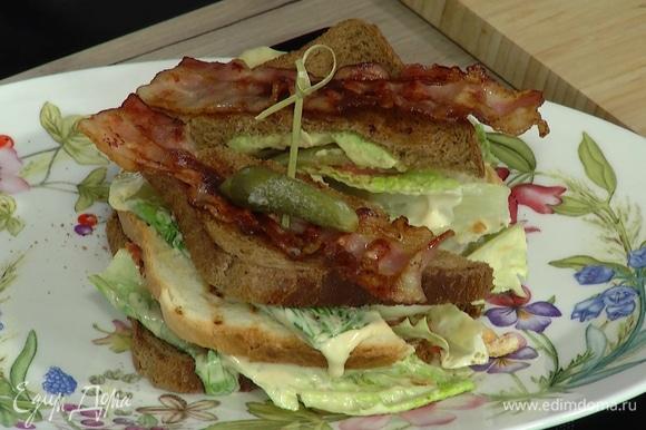 Разрезать сэндвич по диагонали пополам, сверху выложить бекон, по 1 корнишону и закрепить шпажками.