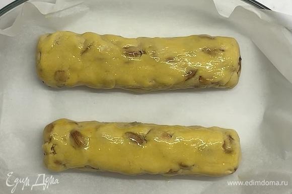 Затем делим на 2 части и формируем колбаски. Сверху смазываем желтком и перекладываем в форму или на противень, застеленный бумагой для выпекания. Отправляем в заранее разогретую до 180°C духовку на 25–30 минут.