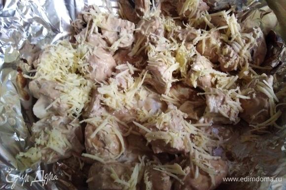 Форму для выпечки застелить фольгой. Выложить грибы с соусом. Посыпать натертым сыром.