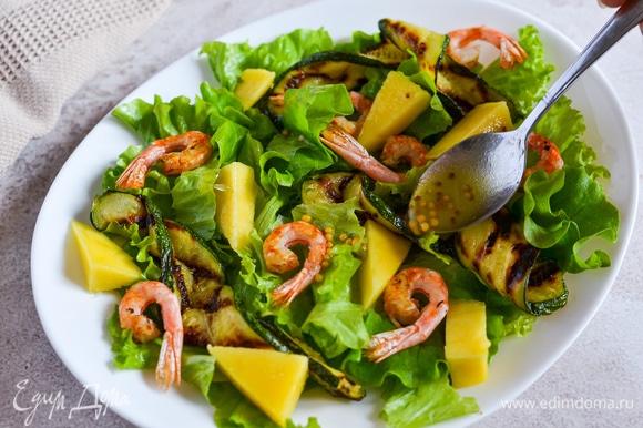 На блюдо выкладываем листья салата, креветки, цукини и манго. Поливаем заправкой.