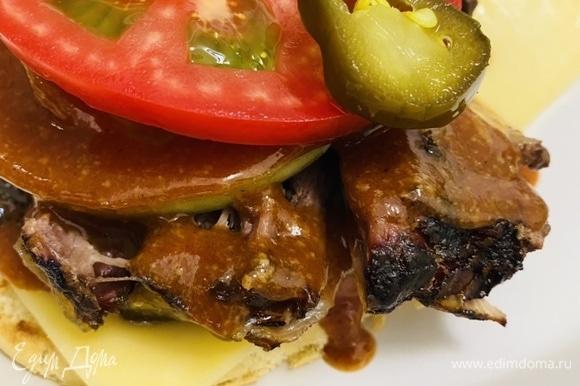 На мясо выложить кольца лука (лук по желанию можно заранее замариновать), помидор и нарезанные кружочки маринованного халапеньо.