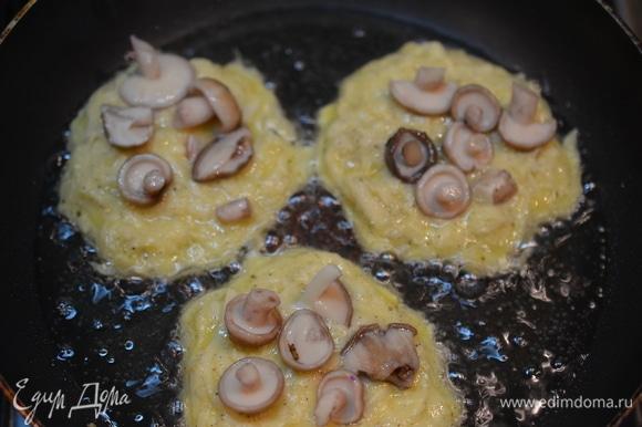 Пока драники жарятся с одной стороны, положите на непрожаренную сторону немного грибов.
