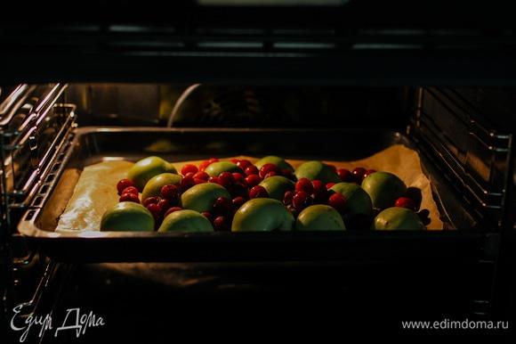 Яблоки разрезать пополам и выложить на противень кожурой вверх, добавить вишню и запекать при 180°C 25–30 минут.