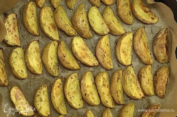 Достаем картошку, переворачиваем дольки на другую сторону и готовим еще 5–10 минут.