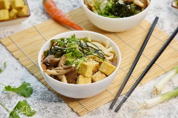По тарелкам раскладываю кубики тофу, грибы, отжатые от лишней влаги, водоросли вакаме, ростки сои для текстуры. Вливаю бульон. Сверху посыпаю суп зеленым луком и добавляю немного острого перца.