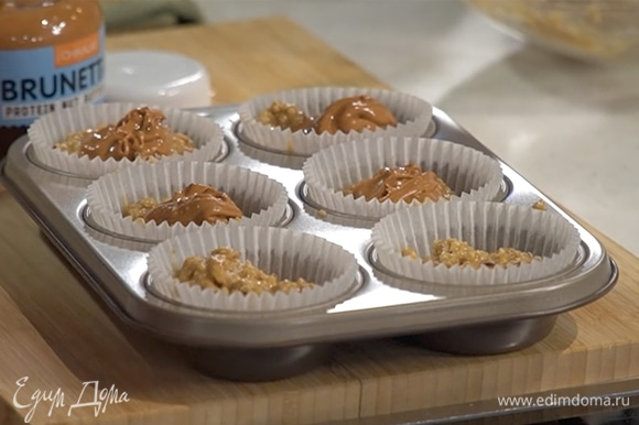 Формочки для маффинов наполовину наполнить тестом, в каждую добавить по одной чайной ложке ореховой пасты, затем разложить оставшееся тесто.