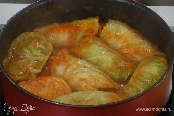 Выложить голубцы в кипящий соус, накрыть крышкой и томить до готовности.