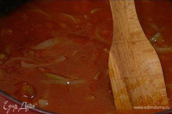 Разогреть в сковороде оставшееся оливковое масло, выложить лук и чеснок и томатную пасту, перемешать и обжарить, затем добавить помидоры в собственном соку, все посолить, влить вино, довести до кипения и дать алкоголю выпариться.