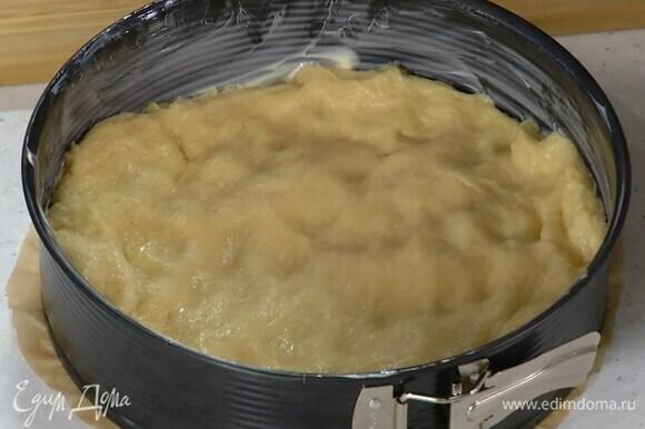 Смазать разъемную форму для выпечки оставшимся сливочным маслом, выложить подошедшее тесто и равномерно распределить.